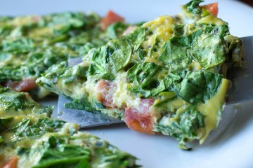 Delicious spinach frittata is loaded with basil, fresh tomatoes, and Parmesan cheese.