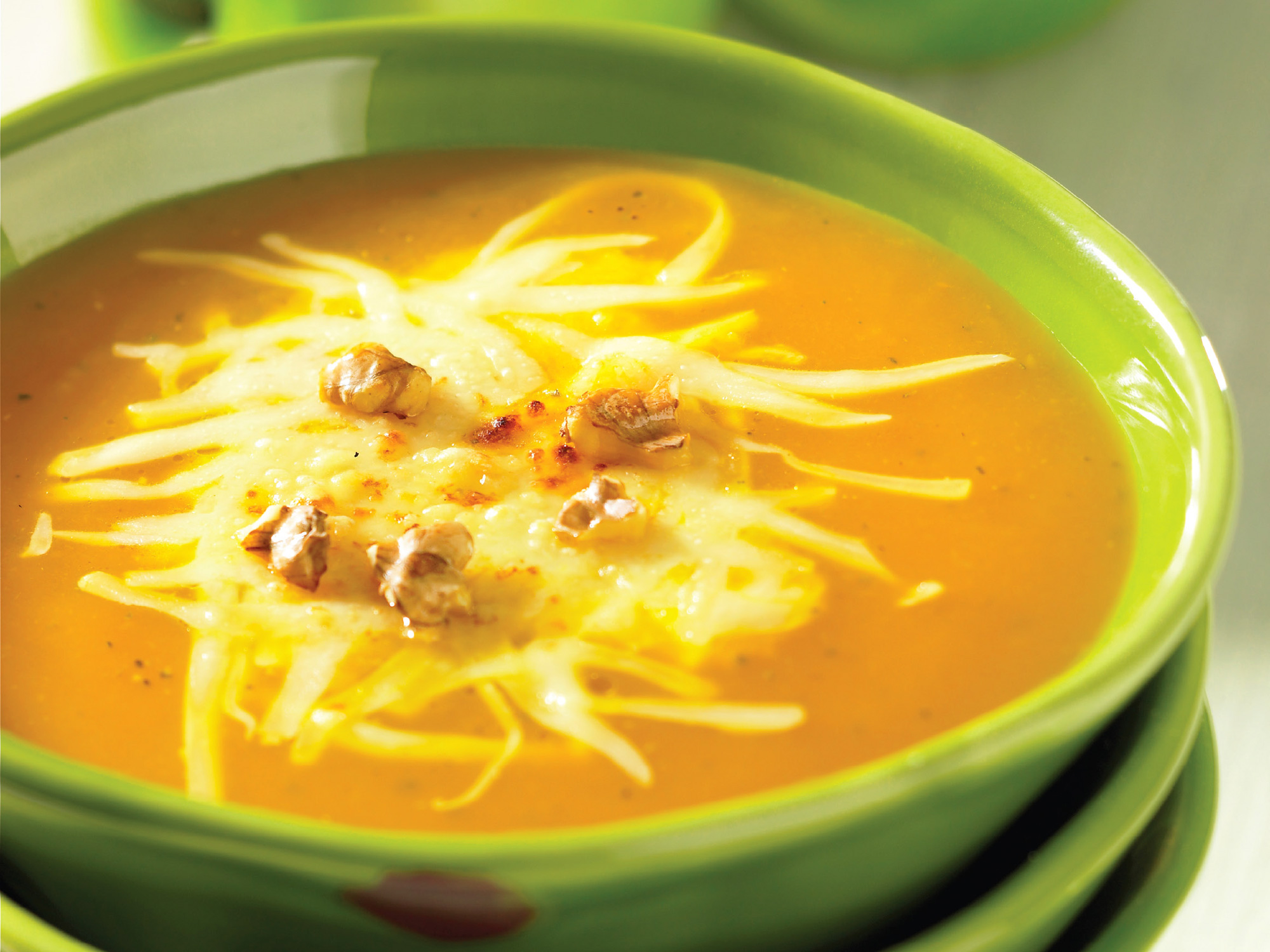 Creamy butternut squash soup topped with Swiss cheese is made in the crockpot.