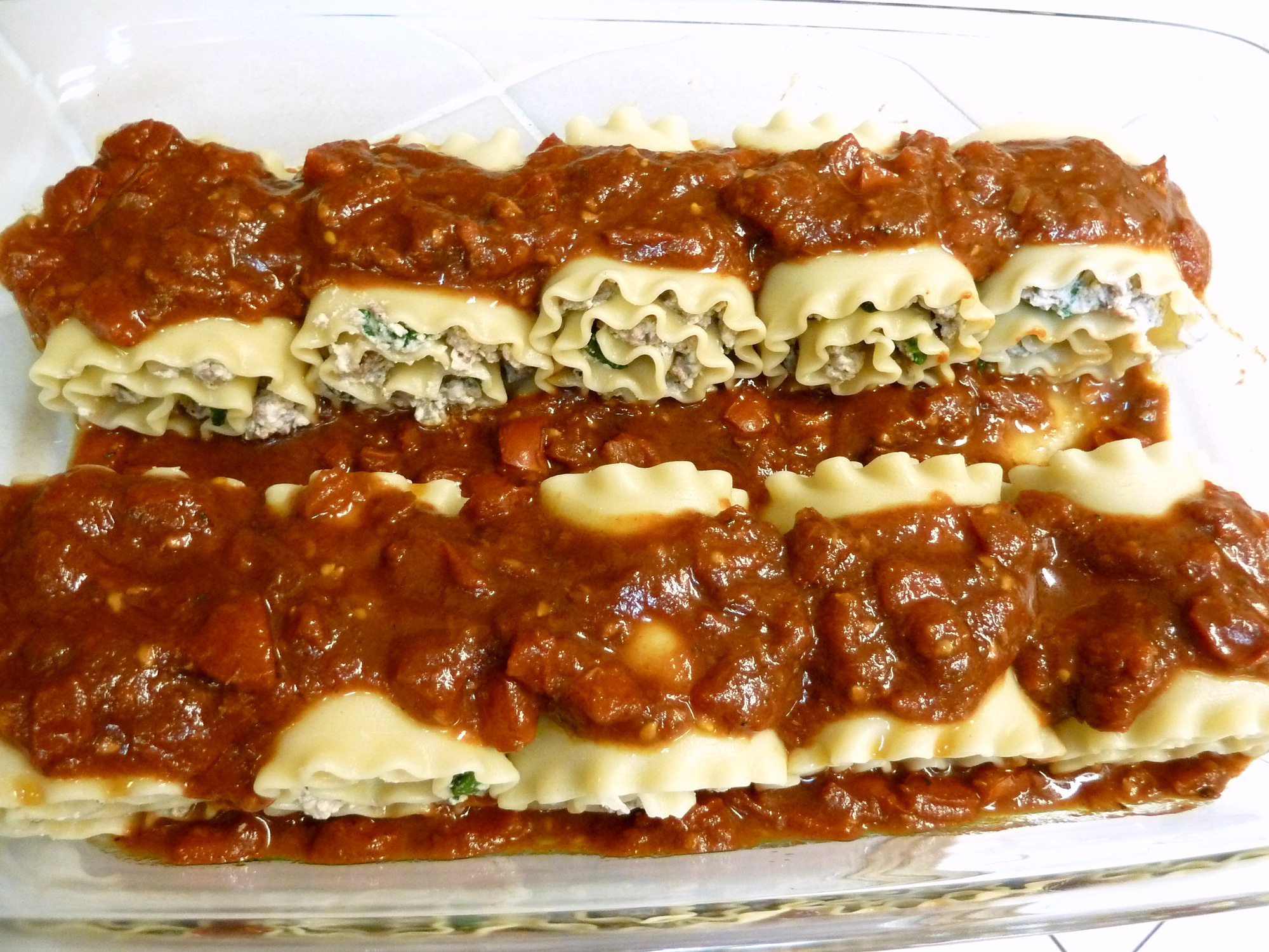 Top lasagna rolls with marinara sauce.