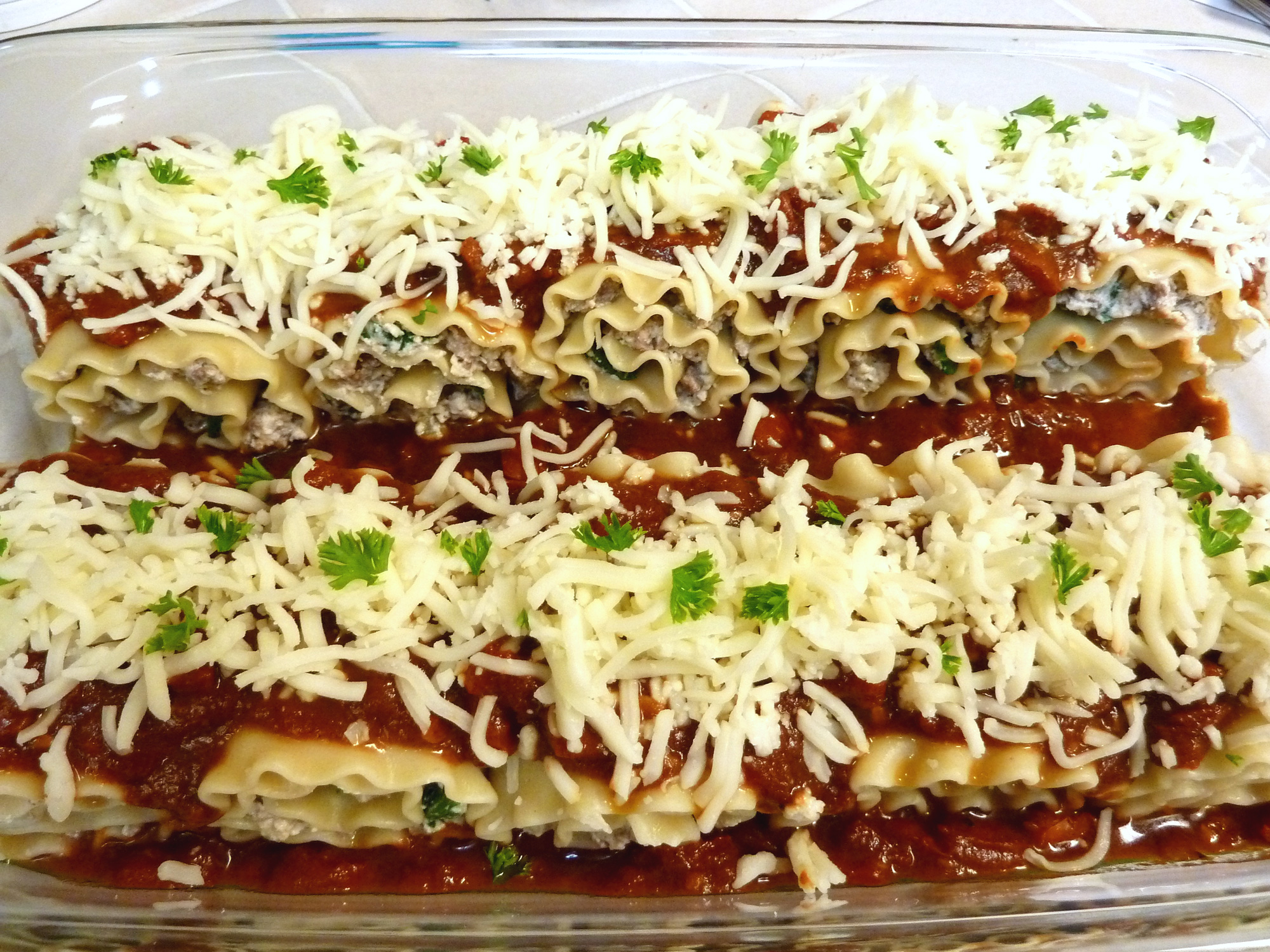 Finish by topping the lasagna rolls with shredded mozzarella cheese.