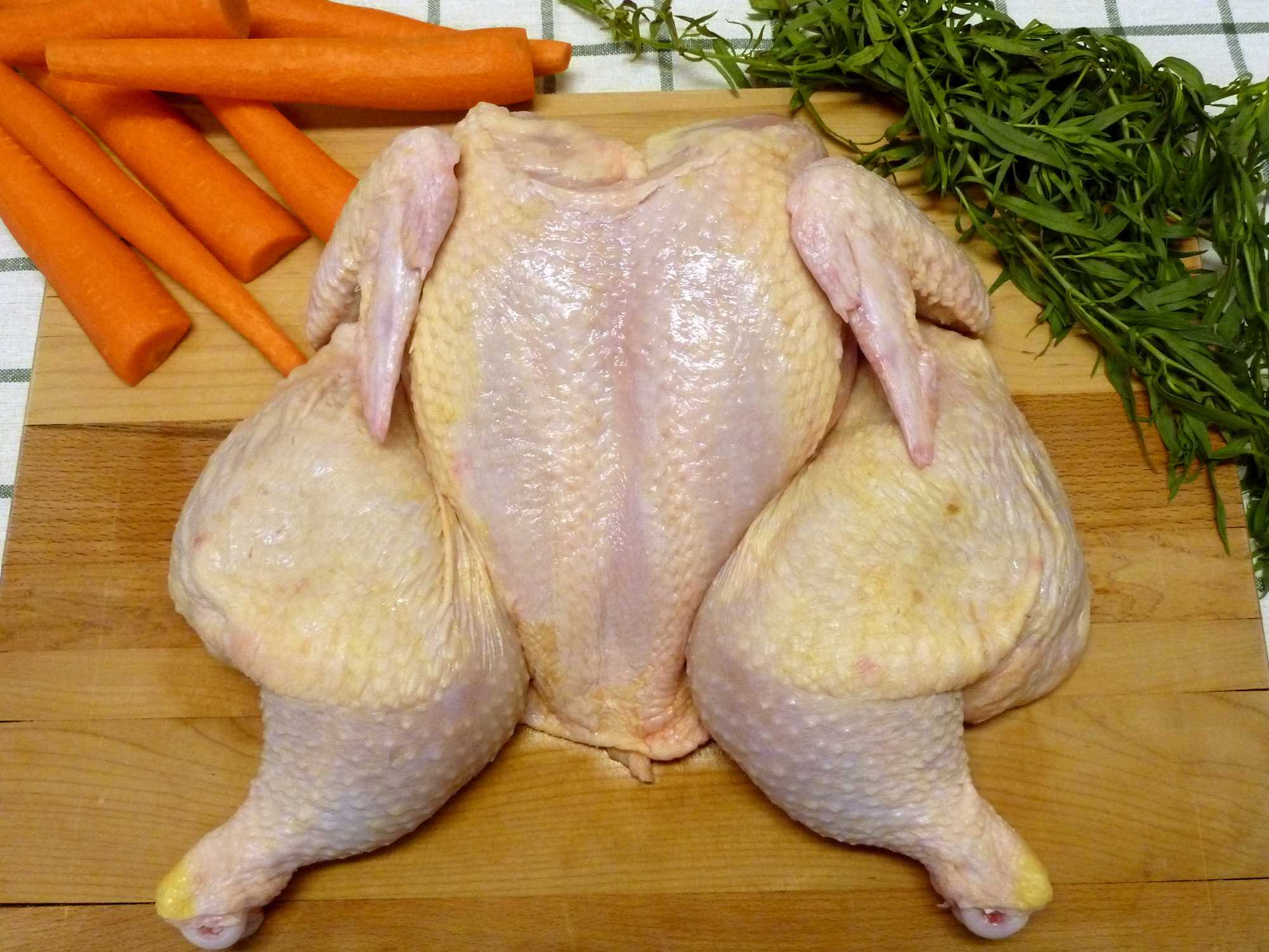 Turn the chicken over and open it up to lie flat. The feet will be pointing outward.