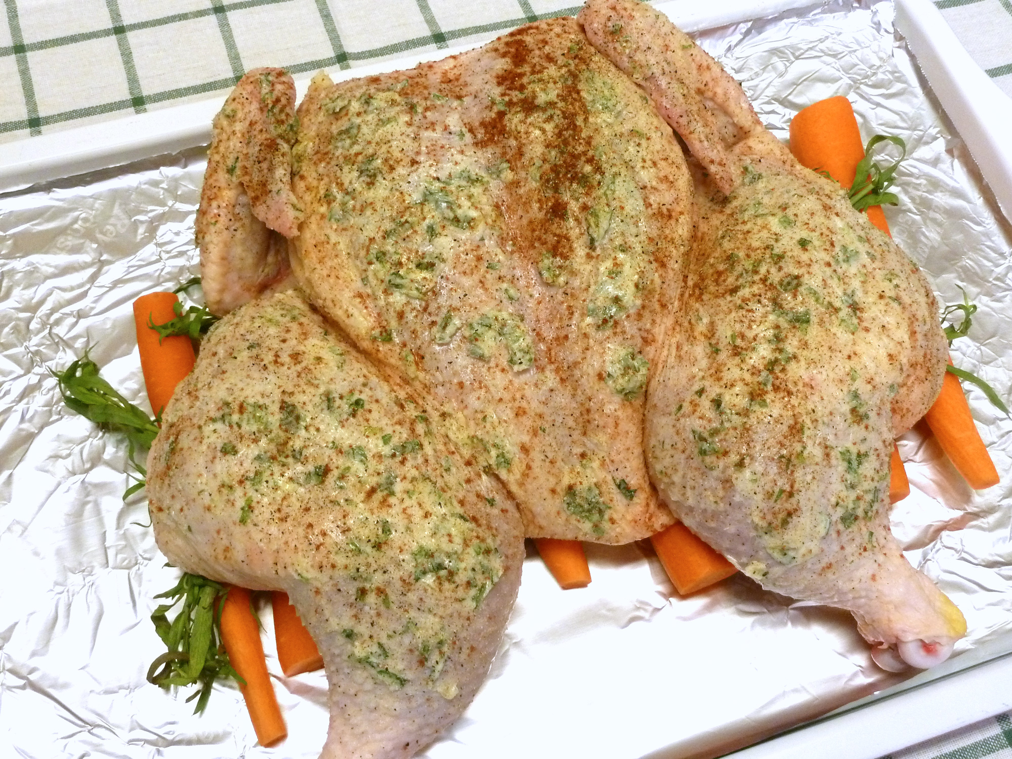 The spatchcocked chicken is rubbed with compound garlic tarragon butter and sprinkled with salt, onion powder, and sweet paprika.