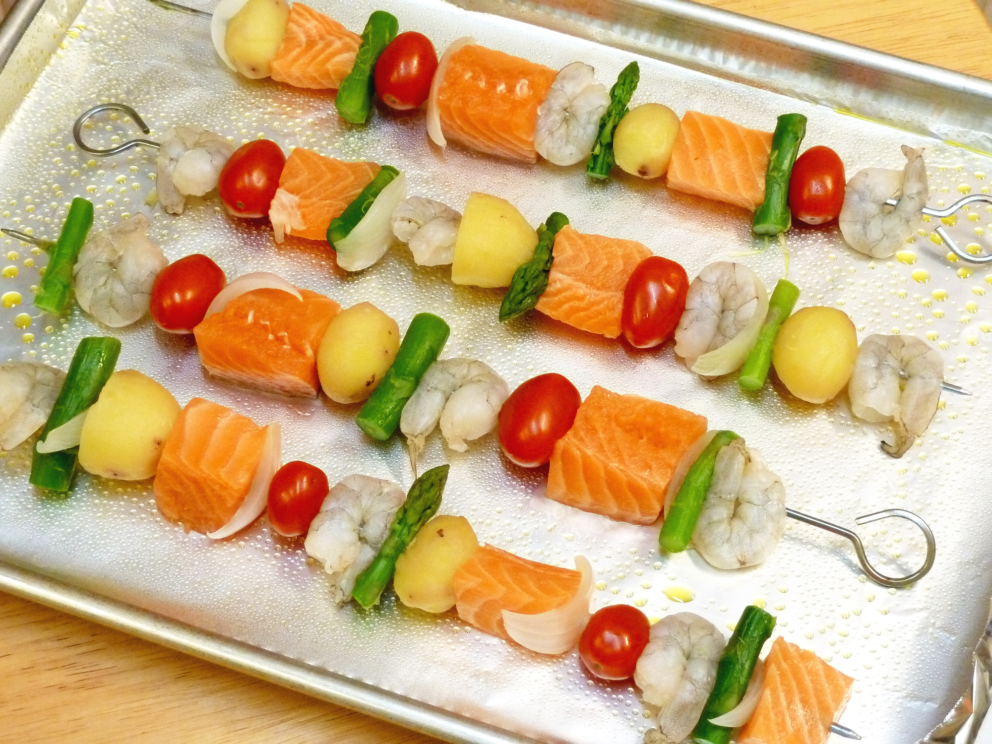 Colorful salmon, shrimp, and vegetables are threaded onto skewers, ready for basting with the special sauce.