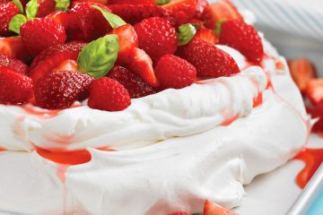 Light and airy Pavlova is topped with berries and tangy whipped cream.
