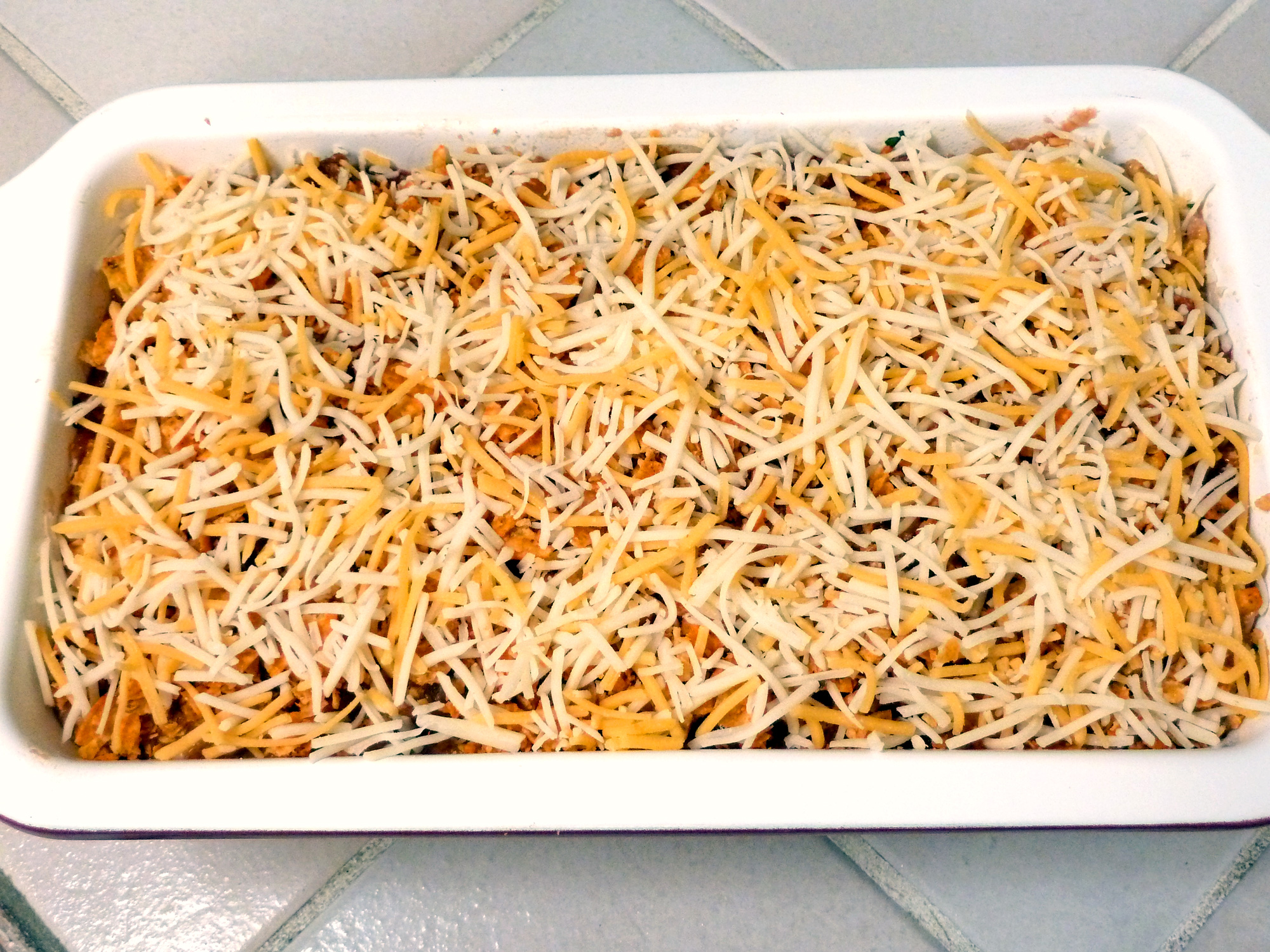 Loco Turkey Meatloaf is topped with salsa, cheese, and more chips. It's ready to go into the oven.