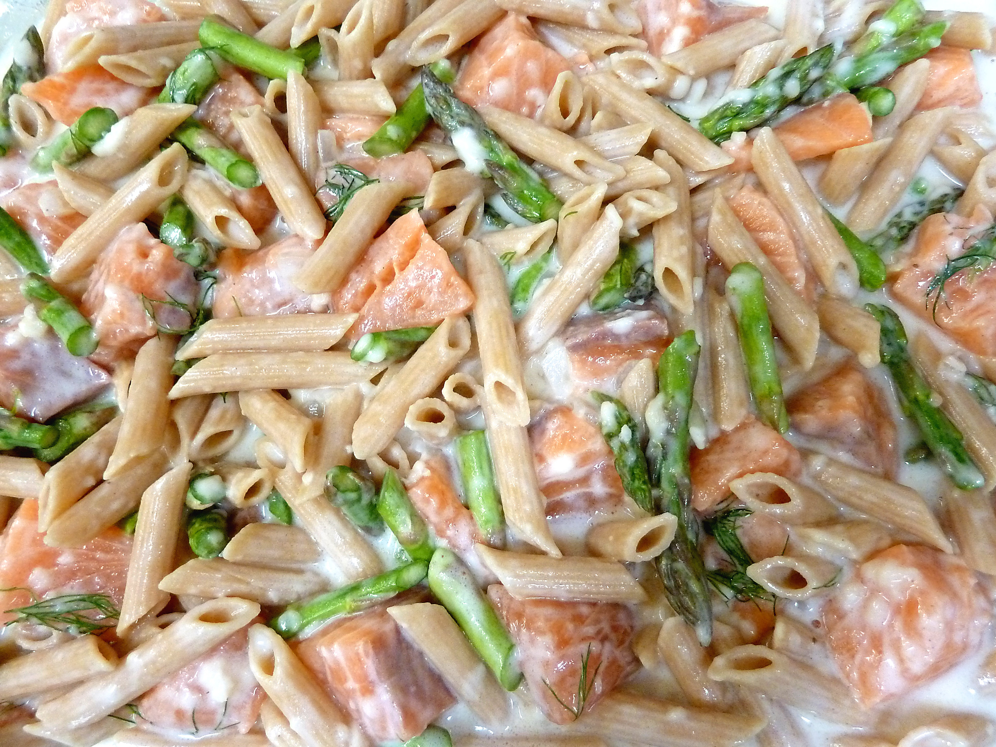 Salmon and fresh asparagus in a creamy seafood sauce is ready to be topped with cheese and toasted panko.