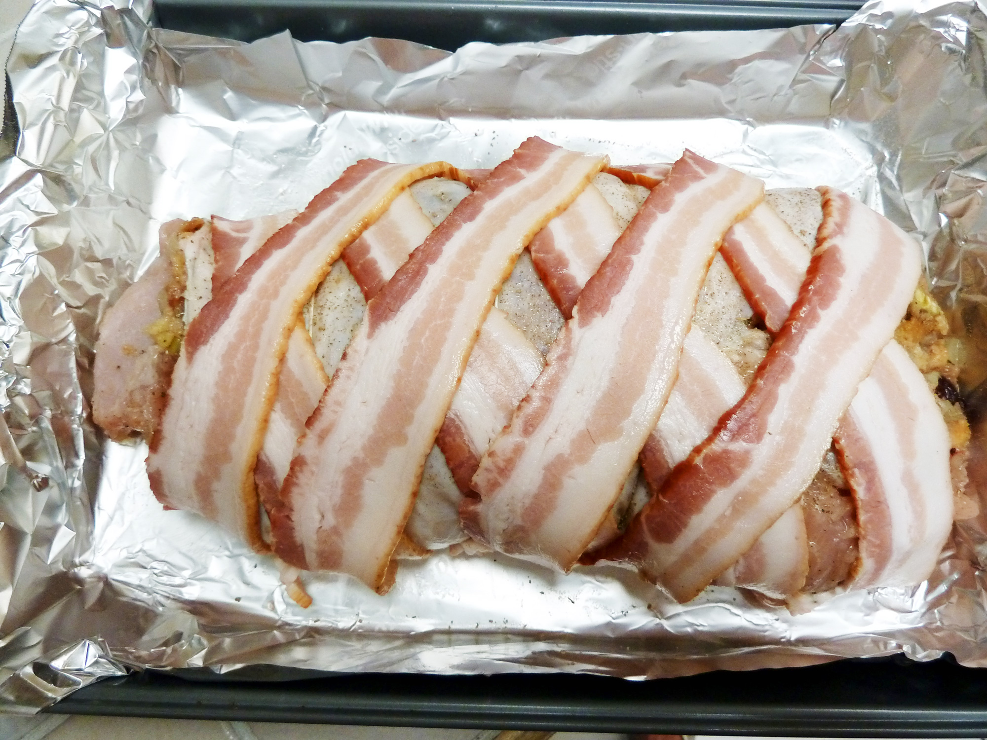 Stuffed turkey breast is wrapped with criss-crossed bacon and ready to go into the oven.