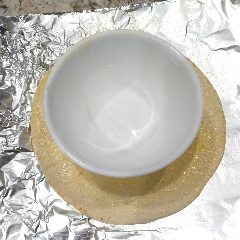 Spray the tortilla with vegetable oil on both sides and place in the center of the foil.